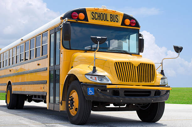 school bus on blacktop with clean sunny background - school bus stock photos and pictures