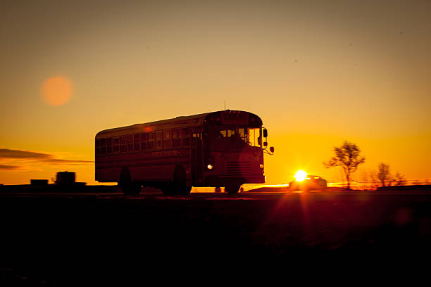 School bus silhouetted at sunrise on the highway. stock photo