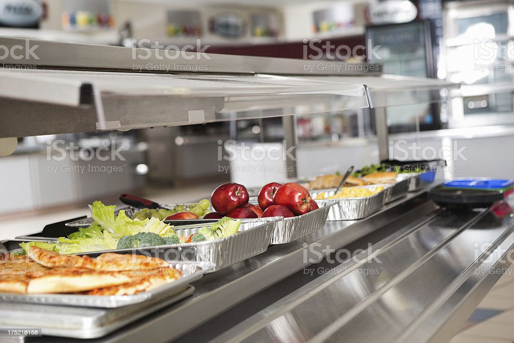 School cafeteria line with healthy and unhealthy food choices stock photo