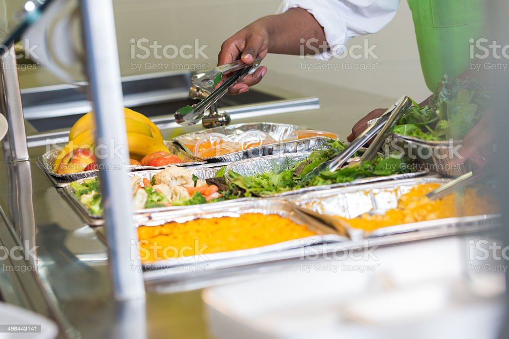 School cafeteria worker serving variety of healthy food stock photo