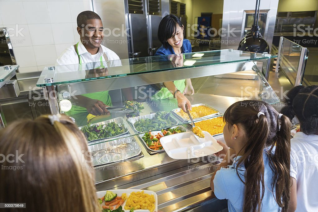 School cafeteria workers offering healthy food options to students stock photo