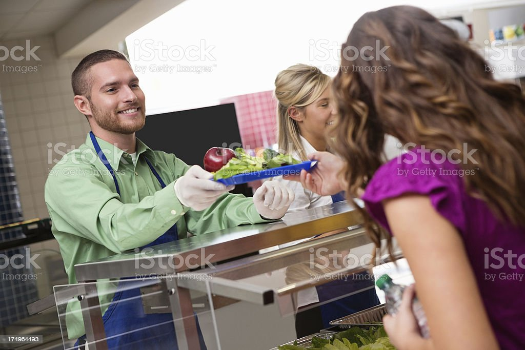 School cafeteria workers serving healthy lunch to junior high student stock photo