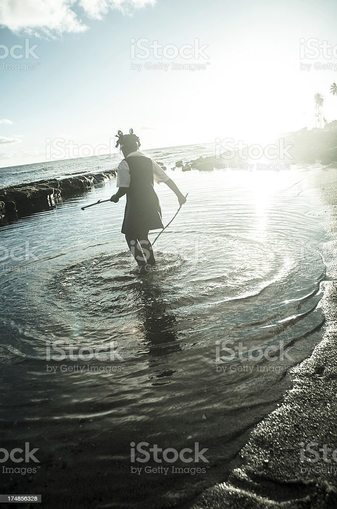 school child playing in outdoor natural pool at sunset stock photo