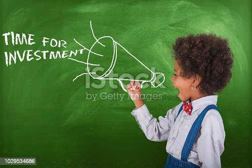 istock School child scream megaphone near school blackboard. 1029534686