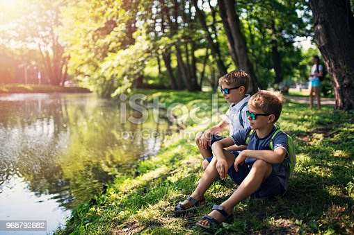 Two boys aged 8 are returning from school through city park. Kids are sitting by a little pond in the park. Sunny day. Nikon D850