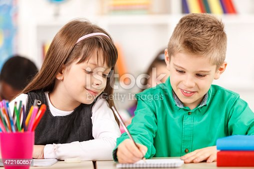 818512928istockphoto School children are sitting in the classroom and writing 472160857