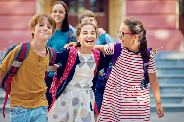 School children are walking at the front of the school and make fun together stock photo