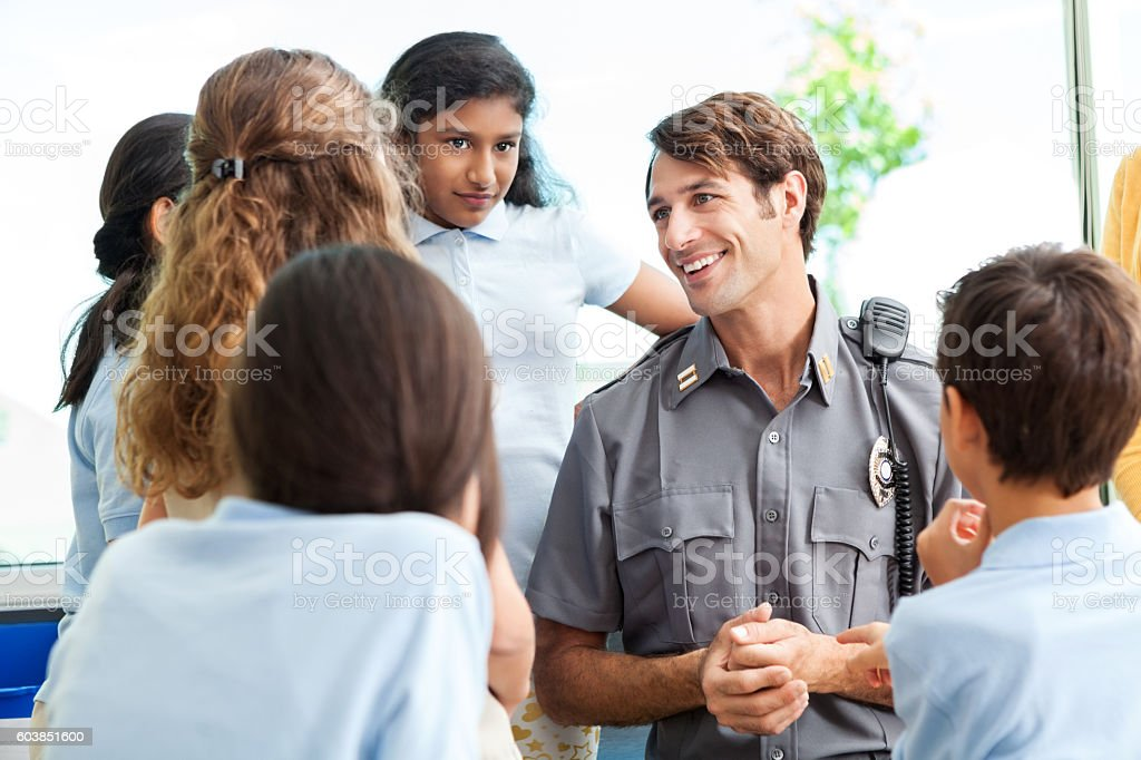 School children ask police officer questions stock photo