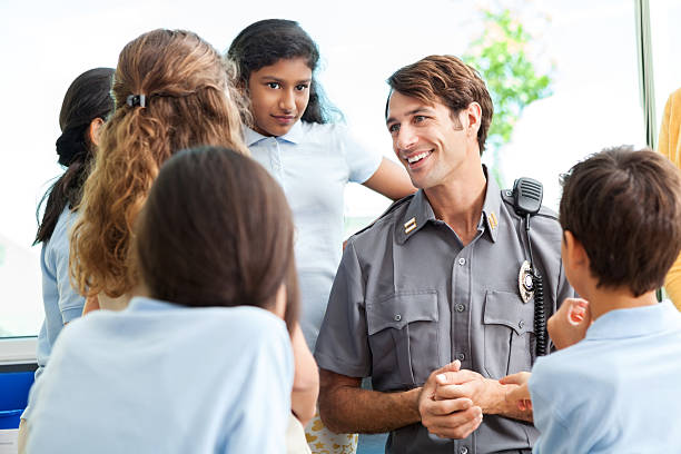 School children ask police officer questions Diverse group of school children gather around mid adult Caucasian security officer. They are asking him questions about his job. The kids are wearing school uniforms. police meeting stock pictures, royalty-free photos & images