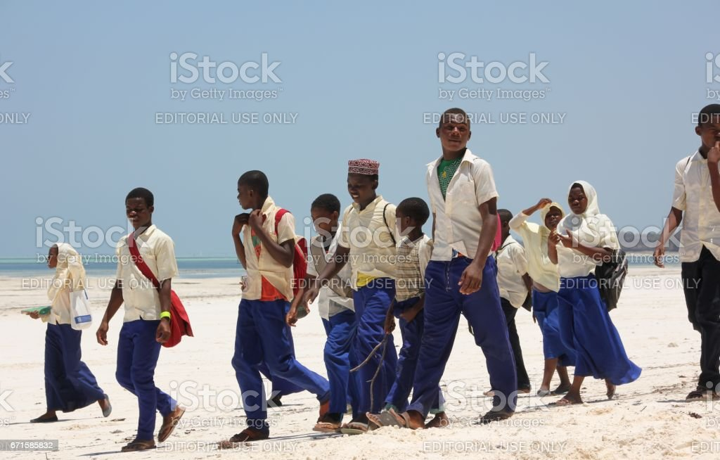 School children in uniform use the beach as their way to school....