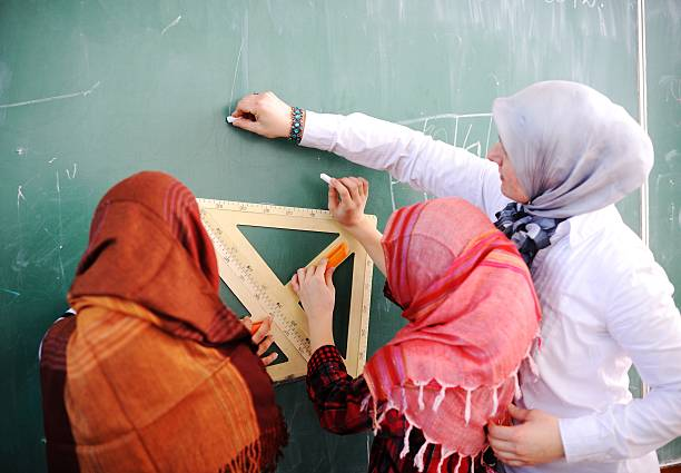 School children being educated at the blackboard Arabic Muslim teacher showing school girls on the classroom board headscarf stock pictures, royalty-free photos & images