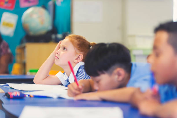 School children bored and tired in class. School children bored and tired in class. They are sitting are desks in a classroom in school uniforms. Some are falling asleep. Multi Ethnic Group illiteracy stock pictures, royalty-free photos & images