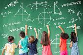 school children drawing math icon on the chalkboard