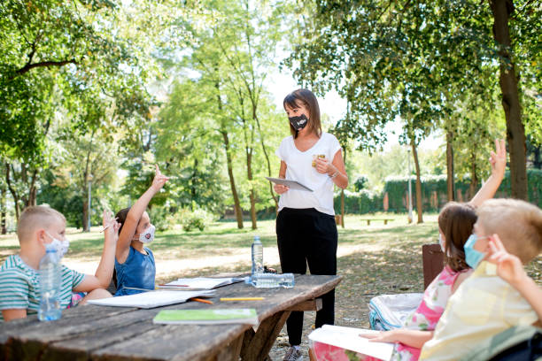 anak-anak sekolah menikmati kelas dengan guru mereka di luar ruangan. - student study outdoor potret stok, foto, & gambar bebas royalti