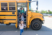 A group of elementary school children exit bus at the end of the school day.