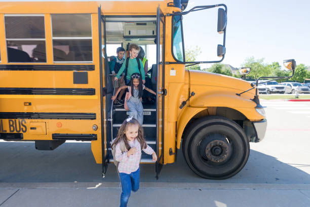 School children exit school bus A group of elementary school children exit bus at the end of the school day. school buses stock pictures, royalty-free photos & images
