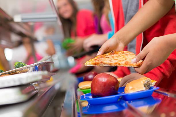 schulkind die lebensmittel in der cafeteria line - kantine stock-fotos und bilder