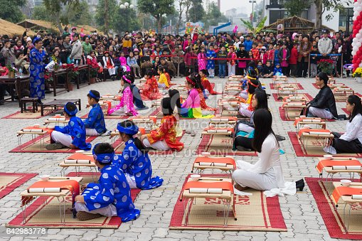 istock Hanoi, Vietnam - Feb 7, 2015: School children in traditional dress Ao Dai learning with calligraphy at Vietnamese lunar New Year celebrating fair day organized at Vinschool, Minh Khai, Hanoi 642983778