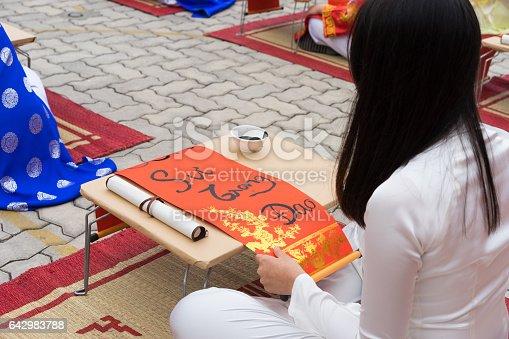 istock Hanoi, Vietnam - Feb 7, 2015: School children in traditional dress Ao Dai learning with calligraphy at Vietnamese lunar New Year celebrating fair day organized at Vinschool, Minh Khai, Hanoi 642983788