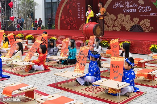 istock Hanoi, Vietnam - Feb 7, 2015: School children in traditional dress Ao Dai learning with calligraphy at Vietnamese lunar New Year celebrating fair day organized at Vinschool, Minh Khai, Hanoi 643024838