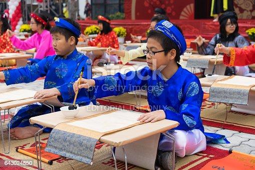 istock Hanoi, Vietnam - Feb 7, 2015: School children in traditional dress Ao Dai learning with calligraphy at Vietnamese lunar New Year celebrating fair day organized at Vinschool, Minh Khai, Hanoi 643024850