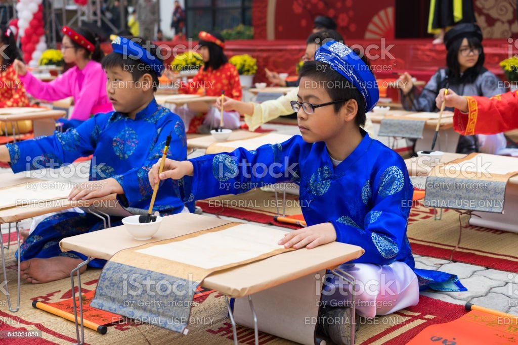 Hanoi, Vietnam - Feb 7, 2015: School children in traditional dress Ao Dai learning with calligraphy at Vietnamese lunar New Year celebrating fair day organized at Vinschool, Minh Khai, Hanoi stock photo