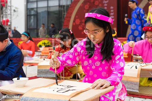 istock Hanoi, Vietnam - Feb 7, 2015: School children in traditional dress Ao Dai learning with calligraphy at Vietnamese lunar New Year celebrating fair day organized at Vinschool, Minh Khai, Hanoi 643024894