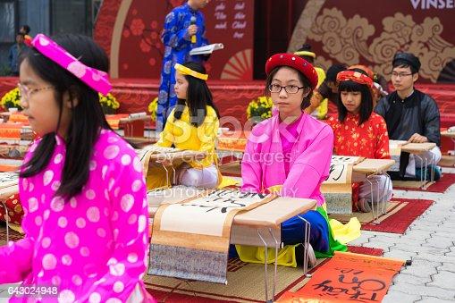 istock Hanoi, Vietnam - Feb 7, 2015: School children in traditional dress Ao Dai learning with calligraphy at Vietnamese lunar New Year celebrating fair day organized at Vinschool, Minh Khai, Hanoi 643024948