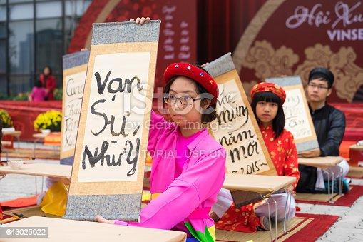 istock Hanoi, Vietnam - Feb 7, 2015: School children in traditional dress Ao Dai learning with calligraphy at Vietnamese lunar New Year celebrating fair day organized at Vinschool, Minh Khai, Hanoi 643025022