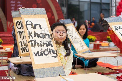 istock Hanoi, Vietnam - Feb 7, 2015: School children in traditional dress Ao Dai learning with calligraphy at Vietnamese lunar New Year celebrating fair day organized at Vinschool, Minh Khai, Hanoi 643025046