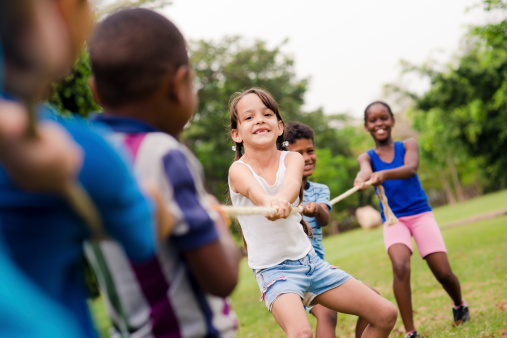 istock school children playing tug of war with rope in park 177506061