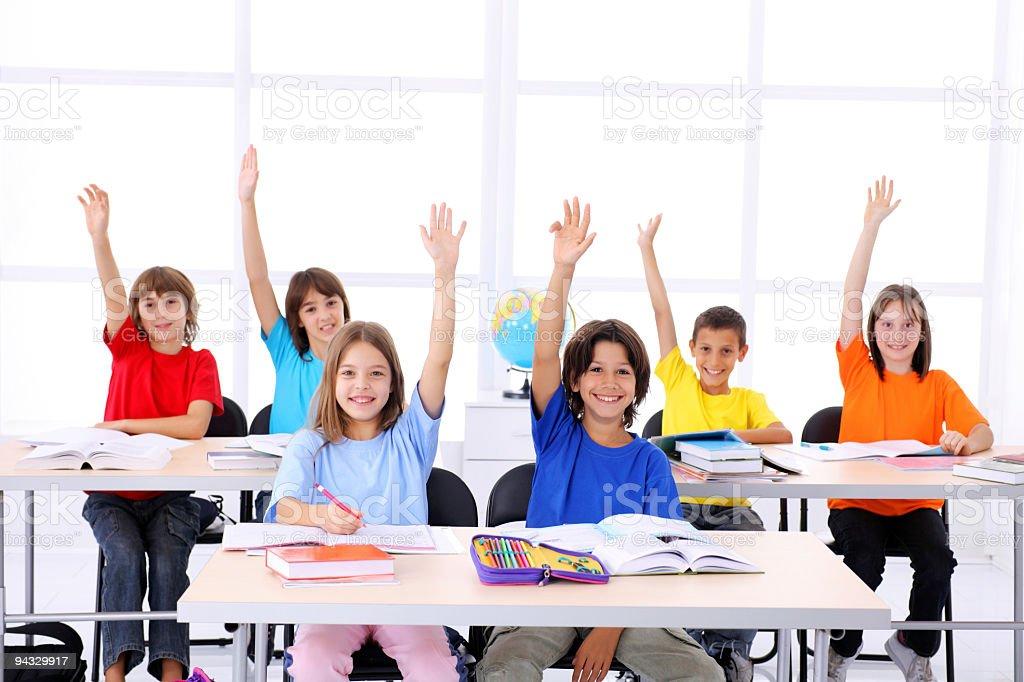 School children raising hands in a modern classroom. royalty-free stock photo
