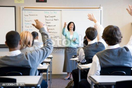 istock School children (14-18) raising hands in class sb10069478l-001