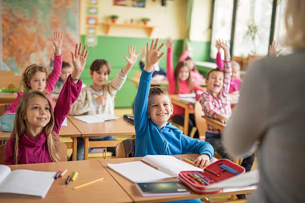 school children plantear sus manos listo para responder a esta pregunta. - escuela primaria fotografías e imágenes de stock