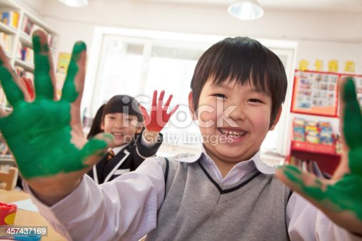 istock School children showing their hands covered in paint 457437169