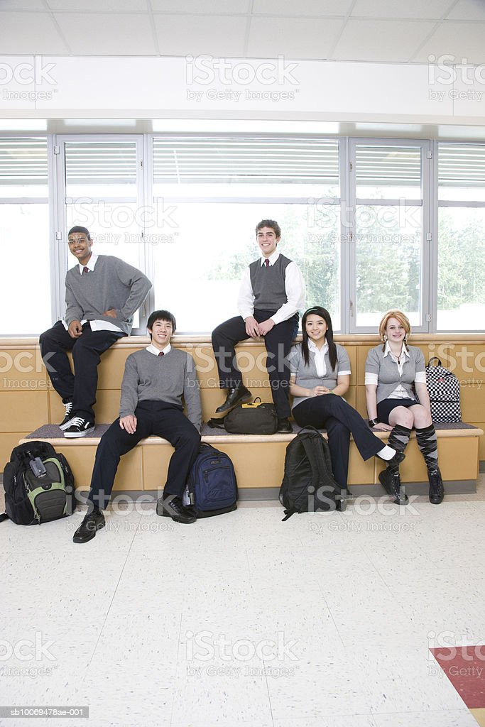 School children (15-19) sitting in school corridor, portrait royalty-free stock photo