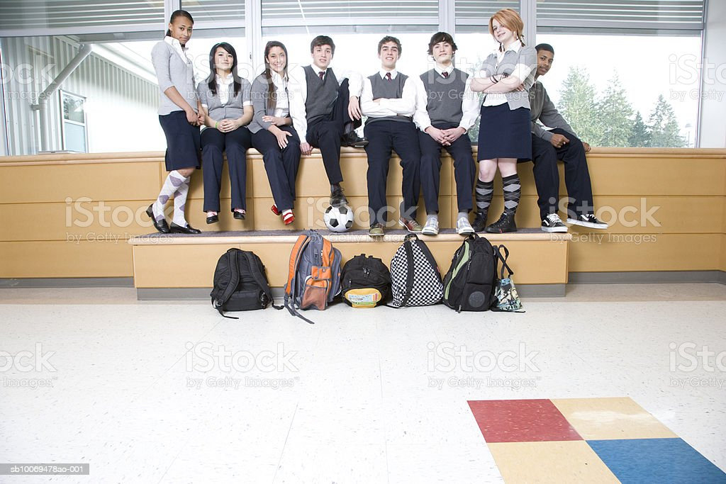 School children (14-19) sitting in school corridor, portrait royalty-free stock photo