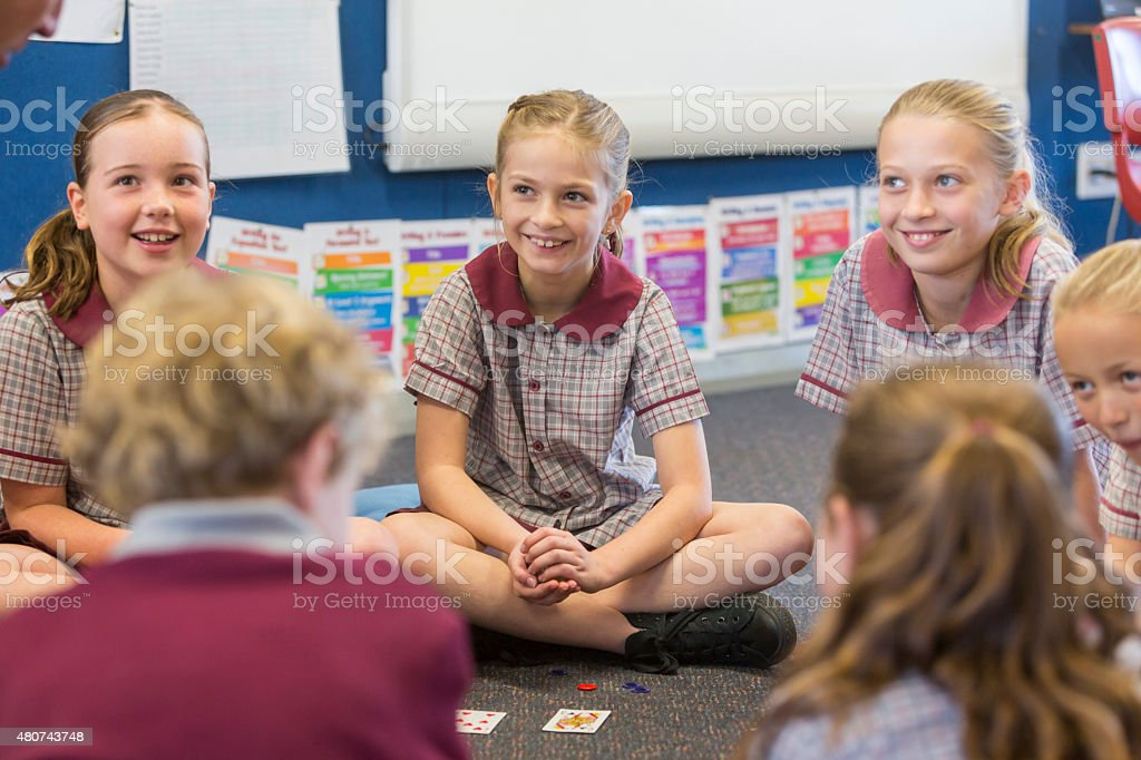 School Children Sitting Playing A Maths Game With Cards stock photo