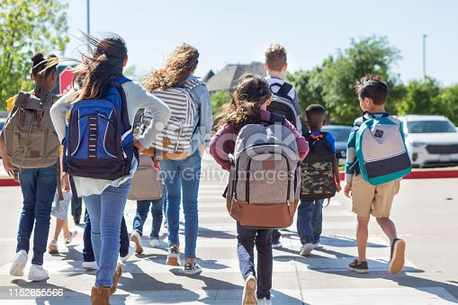 A diverse group of students walk safely on crosswalk to the parking lot.