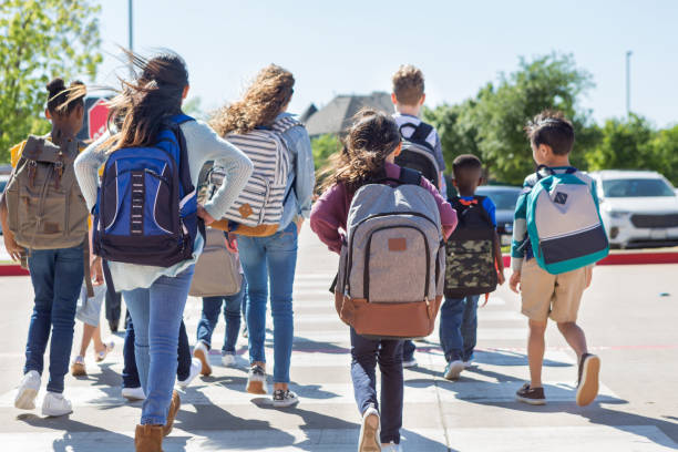 School children walk away from camera in crosswalk A diverse group of students walk safely on crosswalk to the parking lot. field trip stock pictures, royalty-free photos & images