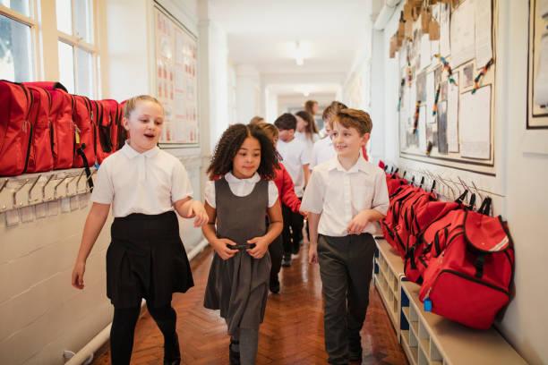 niños de la escuela a pie por el pasillo - regreso a clases fotografías e imágenes de stock