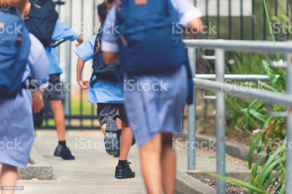 School children walking away. stock photo