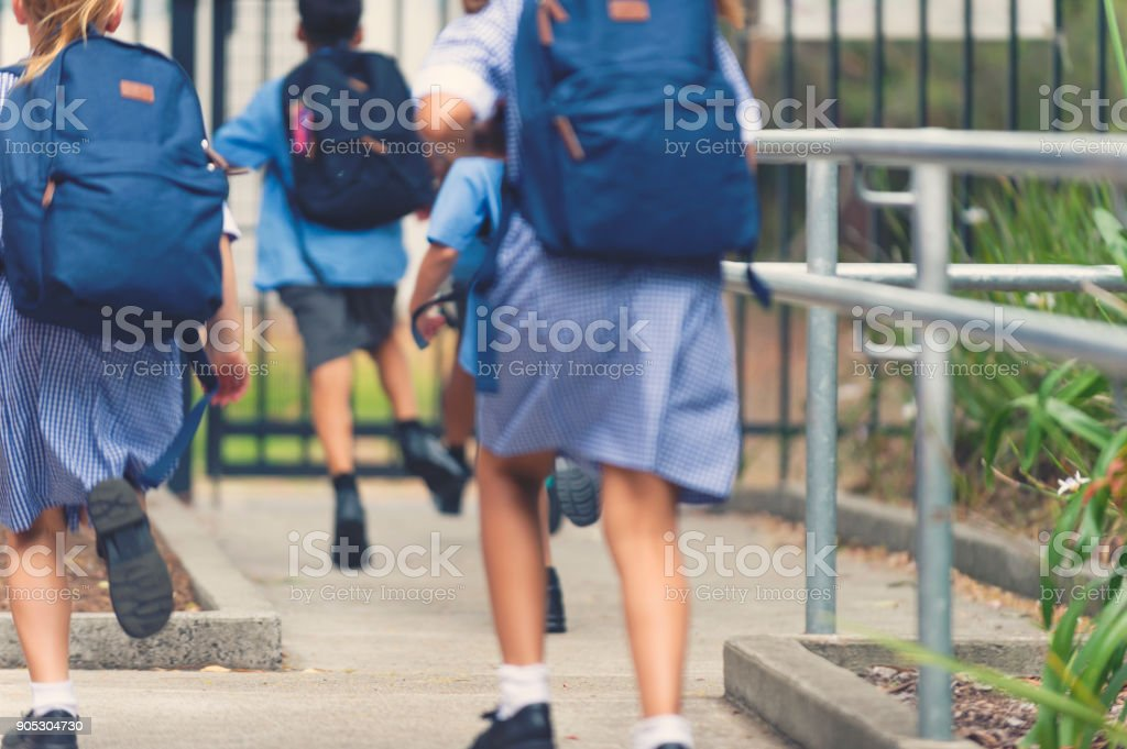 School children walking away. stock photo