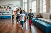 A group of elementary school children wearing casual clothing walk through the hall as their teachers walk behind them. This is a school in Hexham, Northumberland in north eastern England.