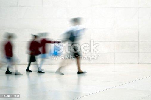 istock School children walking with female teacher, motion blur 108311828
