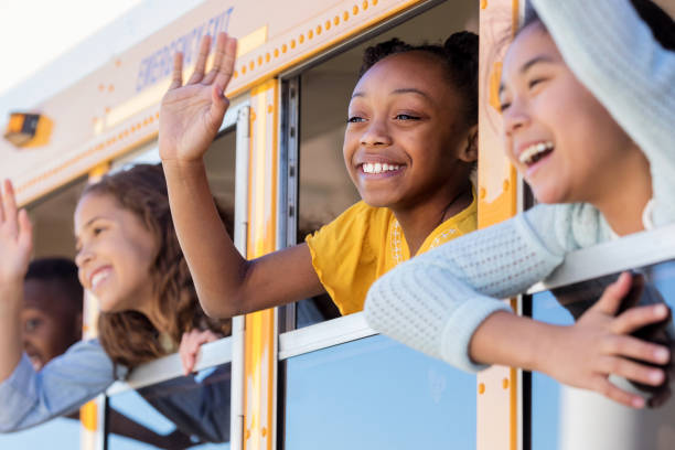 School children wave from school bus As the school bus leaves from school, children wave from their windows on the school bus. field trip stock pictures, royalty-free photos & images