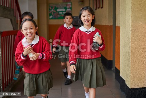 School children holding water bottles while walking in lobby. Happy students are taking break in campus. They are wearing school uniform.
