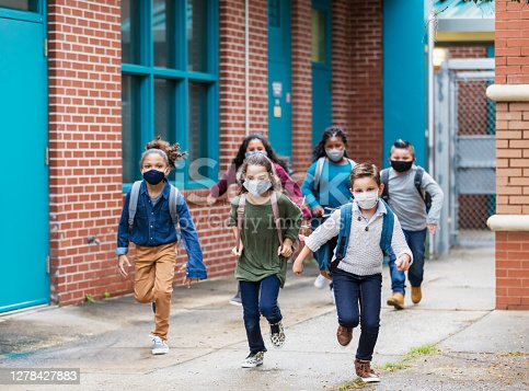 A group of six multi-ethnic elementary school students running outside the school building, carrying backpacks, and wearing face masks. They are back to school during the covid-19 pandemic. The boys and girls are 7 to 10 years old.