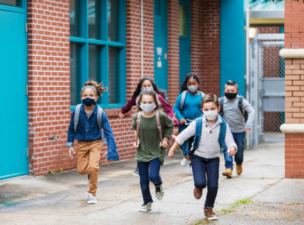 School children with face masks running outside building stock photo