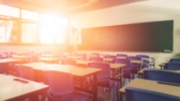 學校教室在模糊的背景下沒有年輕的學生;在校園裡沒有孩子或老師有椅子和桌子的教室裡的模糊景觀。 - 無人 個照片及圖片檔